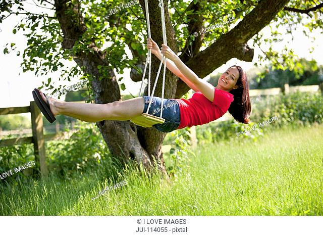 Portrait happy woman swinging on tree swing in sunny rural summer yard, carefree
