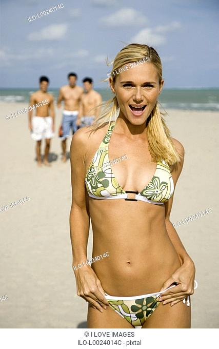 A young woman in a bikini with three male admirers