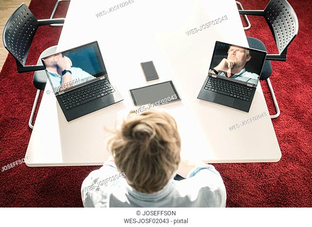 Businessman with two laptops showing images of himself