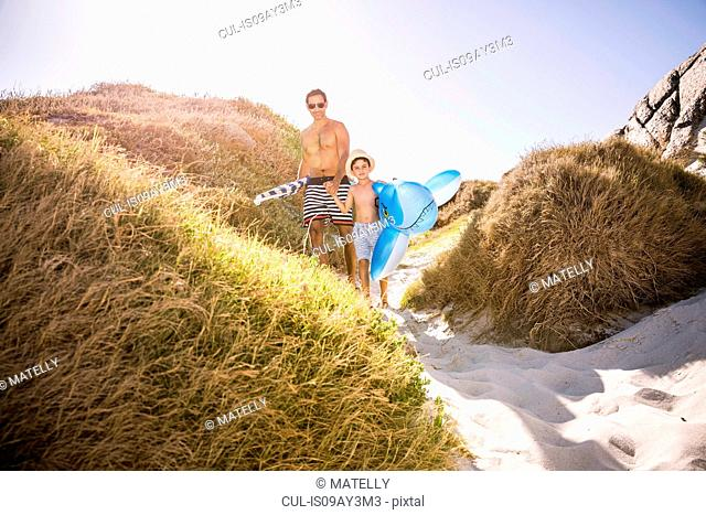 Boy and father walking down sand dune carrying shark inflatable, Cape Town, South Africa