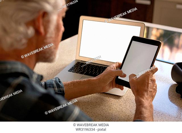 Senior man using digital tablet in kitchen