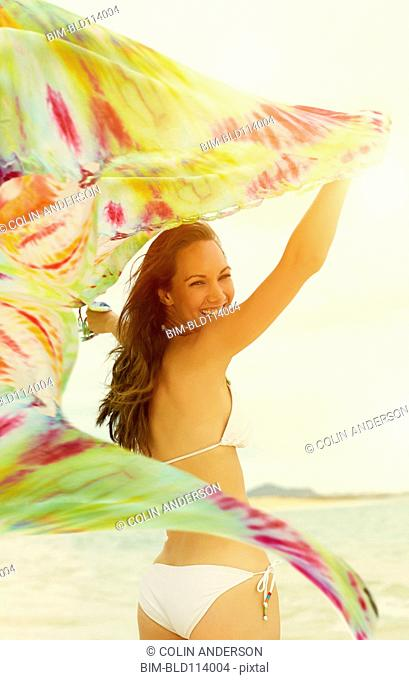 Pacific Islander woman playing with tie die fabric on beach