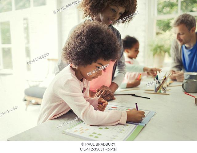 Mother watching daughter coloring in activity book in kitchen