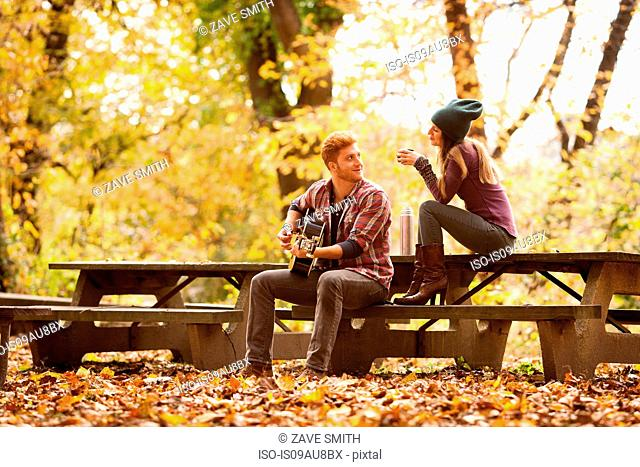 Young couple playing guitar on picnic benches in autumn forest