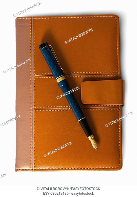 Fountain pen on top of the closed notebook top view isolated on white background