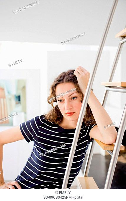 Businesswoman leaning at ladder