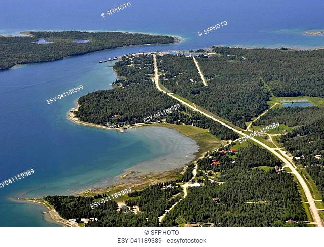 aerial view of the road through a forest area leading to the ferry dock on the end of the road, vacation cottages along the shore of the lake