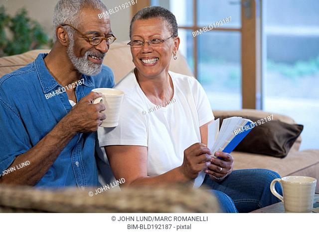 African couple looking at paint swatches on sofa