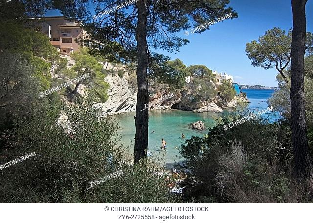 Green water beach, bathers and boats on a sunny day in September in Cala Fornells, Mallorca, Spain