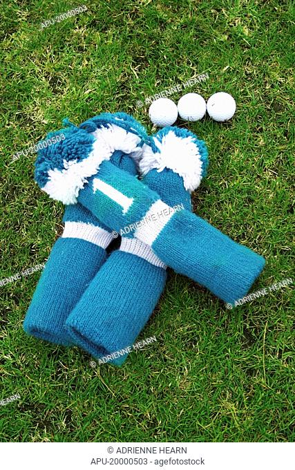 3 golf club head covers next to 3 golf balls at practise area