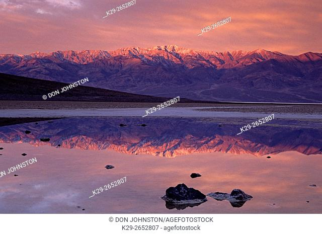 Dawn light on Telescope peak reflected in pond at Badwater Basin, Death Valley National Park, California, USA
