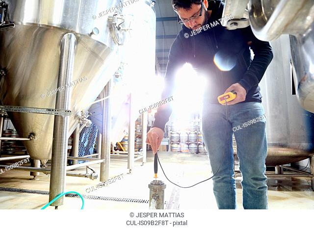 Worker in brewery, checking the temperature of water in brew tank