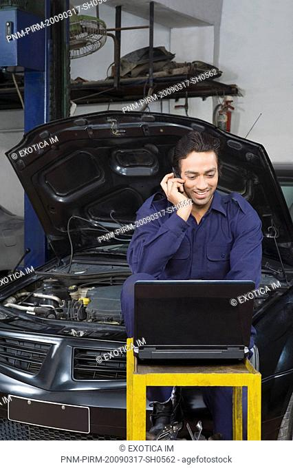 Auto mechanic talking on a mobile phone while using a laptop in a garage