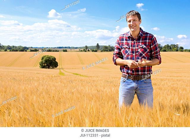 Portrait confident farmer in sunny rural barley crop field in summer