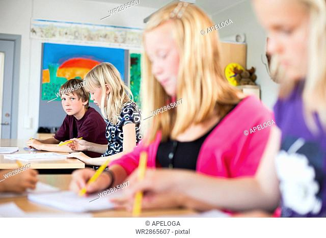 Portrait of serious schoolboy sitting at desk in classroom