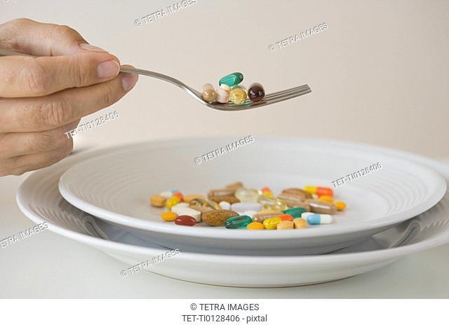 Man eating pills on fork