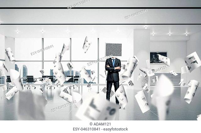 Businessman in suit with monitor instead of head keeping arms crossed while standing among flying papers inside office building. 3D rendering