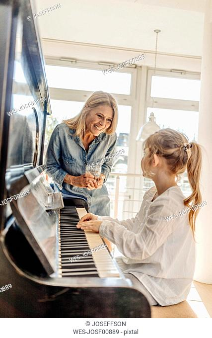 Happy mature woman looking at girl at the piano