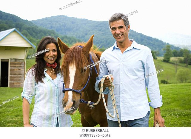 Portrait of a mature man and a woman with a horse