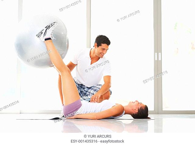 Active woman exercising with fitness ball while trainer looking at her