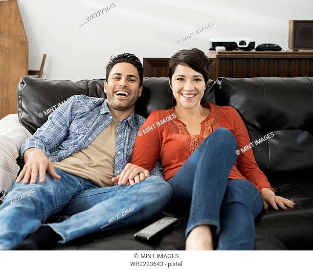 A man and woman sitting on a sofa, side by side, holding hands and watching a screen