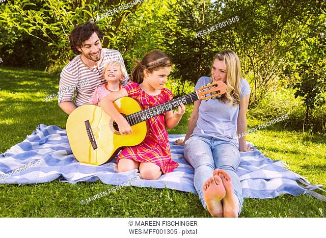 Family on picnic blanket playing guitar