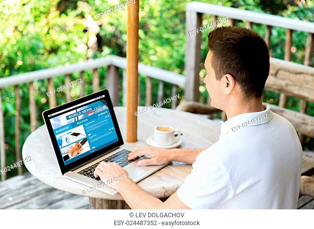 business, mass media, people and technology concept - close up of businessman typing on laptop with news web site on screen outdoors on summer terrace and...