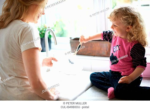 Mother and daughter in kitchen, daughter sitting on work surface helping mother with washing up