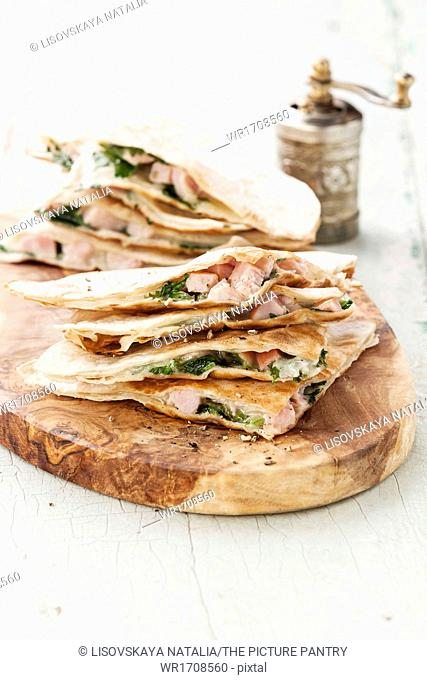 Quesadilla with cheese, meat and vegetables on olive wood cutting board
