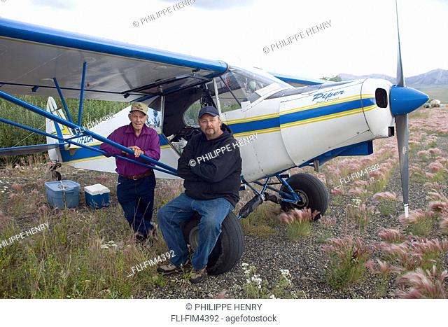 Portrait of Pilots from Alberta in front of their Plane, Dempster Road, Yukon