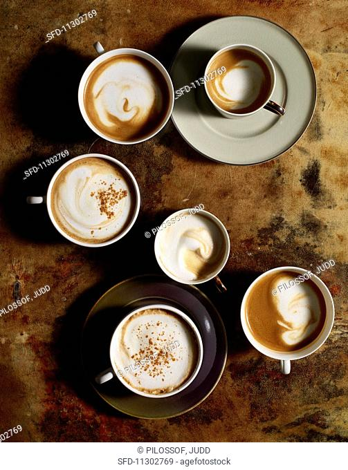 Cups of coffee with milk foam and cinnamon