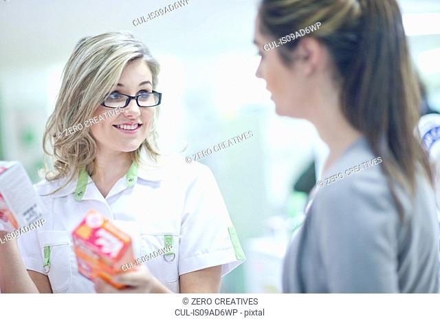 Pharmacist talking to customer, holding boxes of vitamins