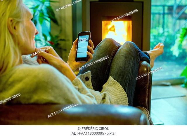 Mature woman relaxing at home with smartphone