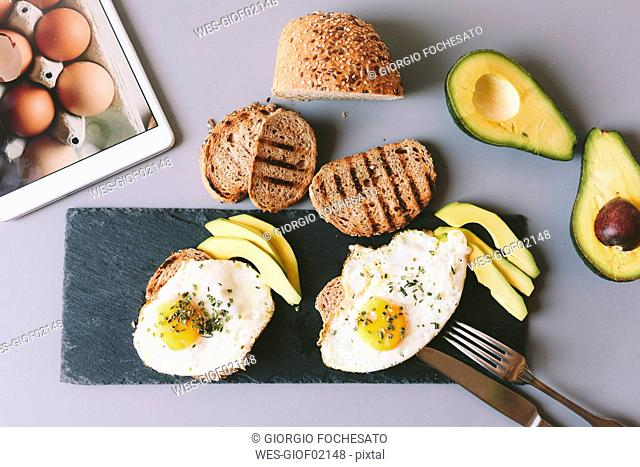 Breakfast with eggs, avovados and toasted bread on a table with digital tablet