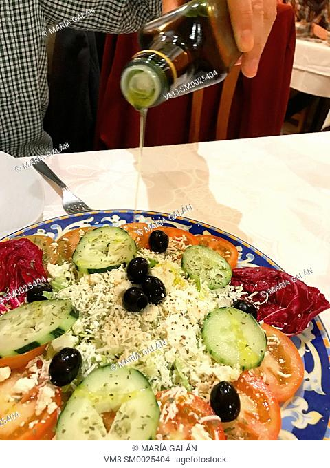 Man dressing a salad with olive oil