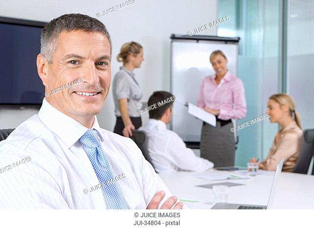 Portrait of smiling businessman in meeting in conference room