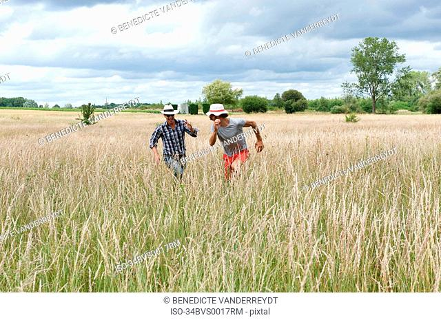 Men running in wheat field
