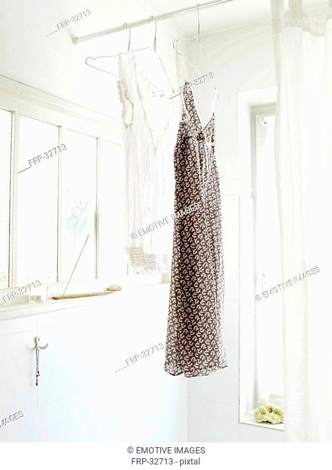Two nightdresses hanging in bathroom