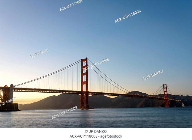 Towers of the Golden Gate Bridge rise above the water at dusk