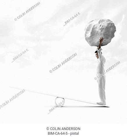 Businessman standing on see saw and holding boulder