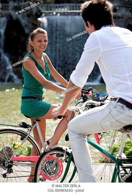 Young couple riding bicycles, Turin, Piedmont, Italy