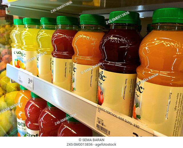 Close-up multicolor juice bottles lined up on the shelf
