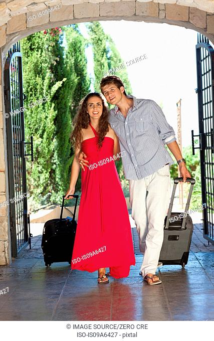 Couple rolling luggage in hotel