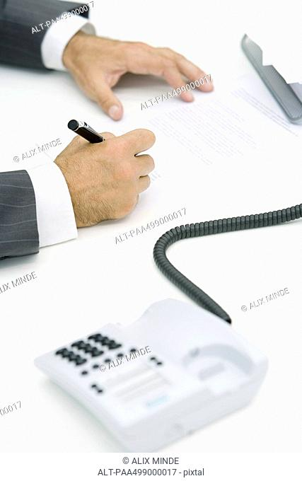 Man signing document, cropped view, landline phone off the hook in foreground