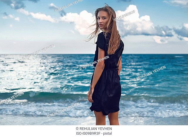Portrait of young woman looking over her shoulder on beach, Odessa, Odessa Oblast, Ukraine