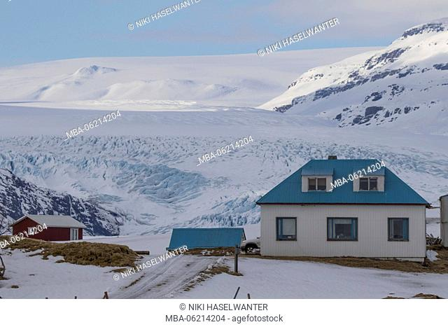 Typical Icelandic house with blue roof, foothills of the Vatnajökull glacier in the background