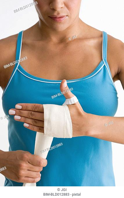 Mid section of woman wrapping hand