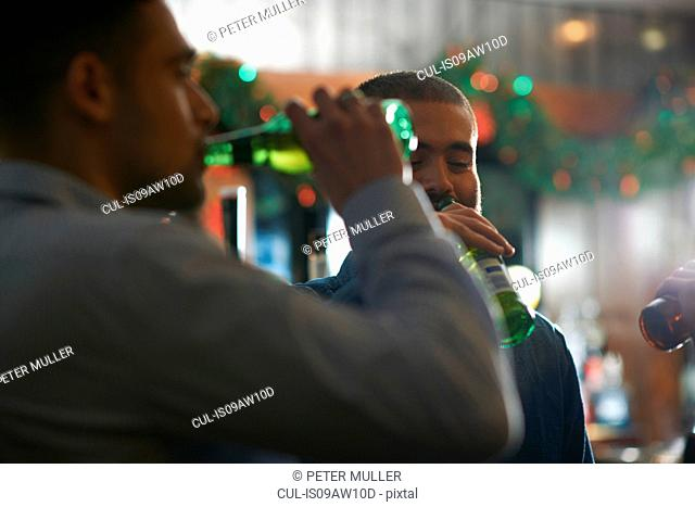 Young men in public house drinking beer from bottles