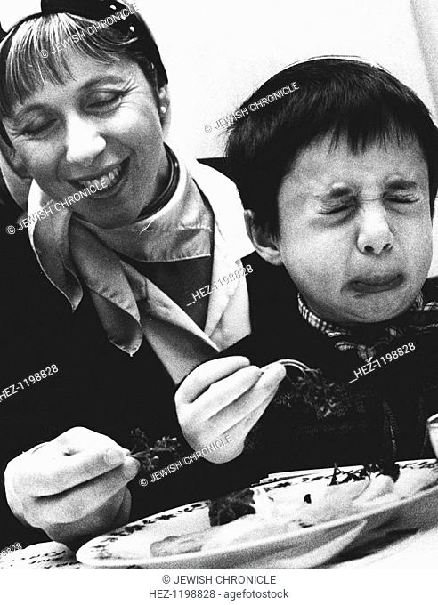 Child tasting bitter herbs at Passover, 1992. Mrs Sachs smiles as Mark Pasha makes a face. Eating bitter herbs is a traditional part of the Seder