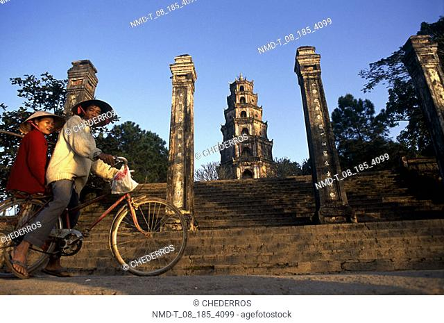 Low angle view of a mid adult couple riding a bicycle in front of a pagoda, Vietnam